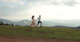 Amore nelle montagne L'uomo e il woiman funzionano lungo la strada all'orizzonte da qualche parte sulla collina mentre il sole sp stock footage