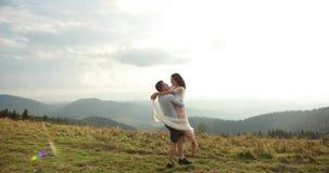 Amore nelle montagne L'uomo gira la donna nelle sue armi che stanno sulla collina con i bei cieli sopra loro archivi video