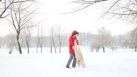 Amore per gli animali domestici - una donna allegra balla e si diverte con il suo cane in un parco innevato dell'inverno stock footage