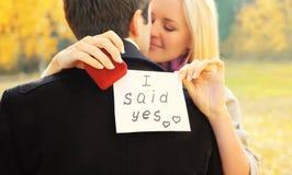 Amore, relazioni, concetto di nozze e di impegno - l'uomo propone una donna per sposare, anello rosso della scatola, giovane copp Fotografia Stock