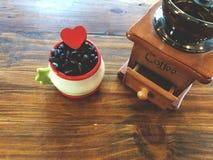 Amore rosso del cuore sui chicchi di caffè scuri dell'arrosto con il macinacaffè manuale Fotografia Stock