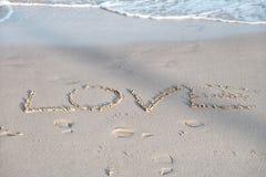 Amore scritto e un segno del cuore sulla bella spiaggia di sabbia con le onde di acqua bianca e la luce del sole immagini stock