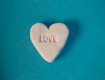 Amore scritto nella forma dolce del cuore della caramella Fotografie Stock