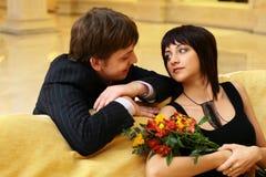 Amores jovenes que se sientan en un sofá Fotos de archivo libres de regalías
