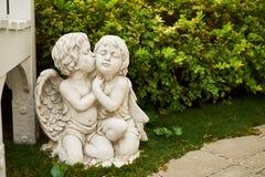 2 amorka obejmują w ogródzie blisko ławki zdjęcie royalty free
