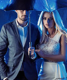 Amorous couple posing on a rainy bacground Royalty Free Stock Images