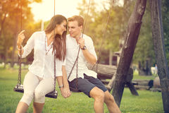 Amorous couple on romantic date. On swings outdoor Royalty Free Stock Image