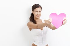 Amorous female holding paper heart smiling. Amorous young female holding paper heart, smiling happily royalty free stock photos