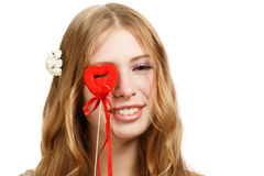 Amorous gaze. Beautiful young smiling woman looking through red souvenir valentine heart isolated on white background Royalty Free Stock Images