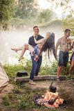 Amorous happy man is raising his girlfriend in the camp royalty free stock image