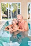 Amorous senior couple in the swimming pool. Amorous senior couple relaxed in the swimming pool on a wellness trip stock image