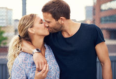 Amorous young couple enjoy a romantic kiss. Amorous attractive young couple enjoy a romantic kiss as they stand arm in arm outdoors in an urban street Royalty Free Stock Photos