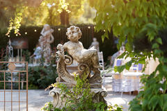Amorskulptur im Garten, nette Amorstatue im Restaurant im Freien Stockfoto