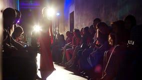 Amortiguar el vestido de noche rojo en un modelo con un retroiluminado almacen de metraje de vídeo