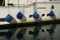 Amortisseurs et réflexion de bateau dans l'eau Photographie stock libre de droits