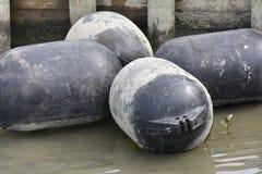 Amortisseurs flottant à côté du quai en bois Photo stock