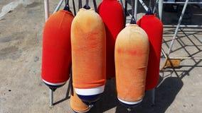 Amortisseurs oranges et rouges pour le bateau Image libre de droits