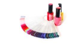 Amostras de verniz para as unhas colorido em uma tabela branca Fotografia de Stock Royalty Free