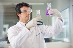 Amostras diferentes de Examining Flasks With do pesquisador imagens de stock royalty free