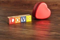 Amour écrit avec des blocs colorés d'alphabet et un bidon Photo stock