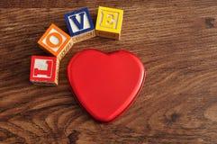Amour écrit avec des blocs colorés d'alphabet et un bidon Images libres de droits