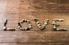 Amour écrit avec des pierres sur un en bois Photographie stock