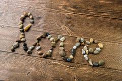 Amour écrit avec des pierres sur un en bois Photos stock