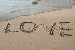 Amour écrit dans le sable Photographie stock libre de droits