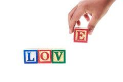 AMOUR écrit dans les blocs colorés d'alphabet d'isolement sur le blanc Photos stock