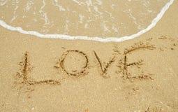 Amour écrit en sable Photos stock