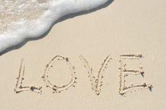 Amour écrit en sable sur la plage Photos stock