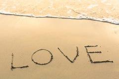 Amour - écrit manuellement sur la texture du sable de mer Voyage Photos stock