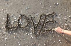 AMOUR écrit sur la plage avec la main Photos stock