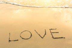 Amour - écrit sur la plage sablonneuse avec la vague molle Résumé Photo libre de droits
