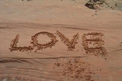 Amour écrit sur le sable Photos stock