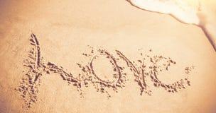 Amour écrit sur le sable avec des vagues Images stock