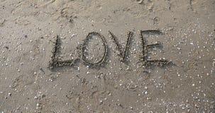 AMOUR écrit sur le sable de plage Images stock
