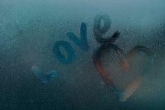 Amour écrit sur le verre par temps pluvieux Image stock