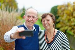 Amour au foyer Couples supérieurs heureux collant entre eux et faisant le selfie Image stock