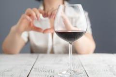 Amour au vin Les mains femelles de prise au coeur signent contre le verre de vin Photographie stock