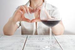 Amour au vin Les mains femelles de prise au coeur signent contre le verre de vin Photographie stock libre de droits