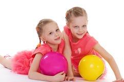 Amour avec du charme de deux soeurs pour jouer la boule. Photos libres de droits