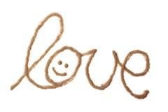 Amour avec le smiley écrit avec le sable Images stock