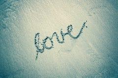 Amour bleu de couleur verte de vintage manuscrit sur la plage sablonneuse Images libres de droits