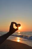 Amour Coeur en pierre dans la main à la lumière du coucher du soleil Images stock
