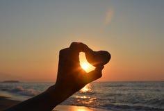 Amour Coeur en pierre dans la main à la lumière du coucher du soleil Image libre de droits