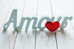 Amour, amour coeur rouge et l'intrigue amoureuse de mot sur un fond en bois blanc Image libre de droits
