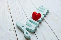 Amour, amour coeur rouge et l'intrigue amoureuse de mot sur un fond en bois blanc Photo stock