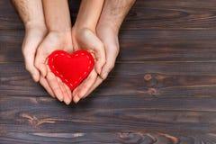 Amour, concept de la famille Fermez-vous des mains de l'homme et de femme tenant le coeur en caoutchouc rouge ensemble Photographie stock