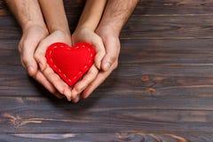 Amour, concept de la famille Fermez-vous des mains de l'homme et de femme tenant le coeur en caoutchouc rouge ensemble Image libre de droits